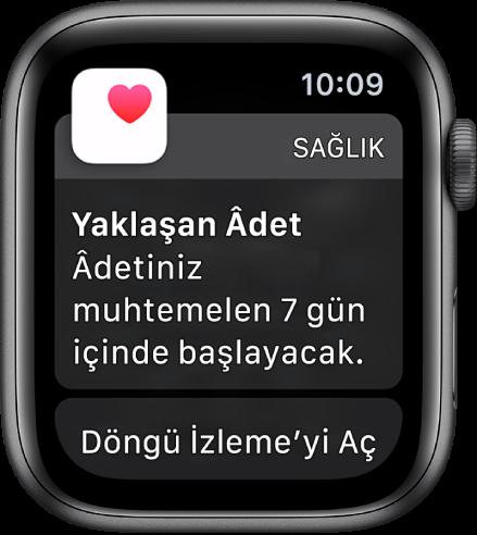 """Şu yazının bulunduğu bir döngü tahmini ekranını gösteren Apple Watch: """"Yaklaşan Âdet. Âdetiniz 7 gün içinde başlayabilir."""" Döngü İzleme'yi Aç düğmesi en altta görünür."""