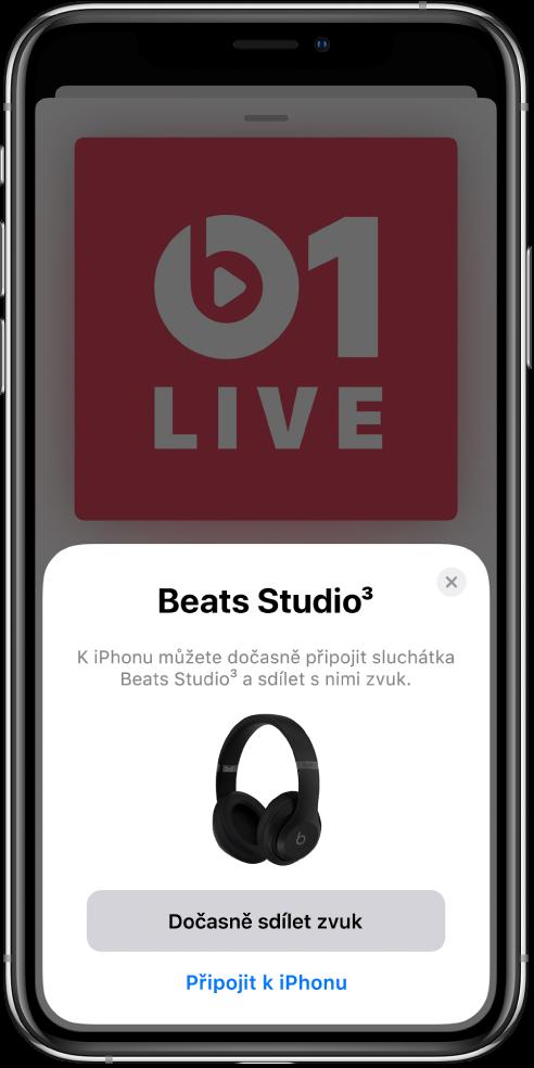 Displej iPhonu sobrázkem sluchátek Beats. Udolního okraje obrazovky je vidět tlačítko dočasného sdílení zvuku.