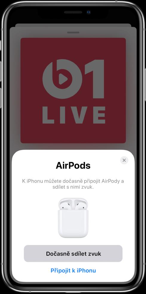 Obrazovka iPhonu sobrázkem AirPodů votevřeném nabíjecím pouzdře. Udolního okraje obrazovky je vidět tlačítko dočasného sdílení zvuku.