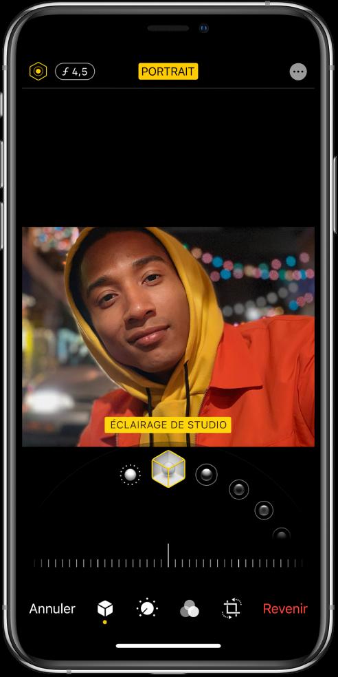 L'écran Modifier d'une photo prise en mode Portrait. En haut à gauche de l'écran se trouvent les boutons «Intensité de l'éclairage» et «Réglage de la profondeur». En haut, au centre de l'écran, le bouton Portrait est activé et en haut à droite se trouve le bouton Modules. La photo est au centre de l'écran; sous celle-ci se trouve un curseur permettant de choisir l'effet d'éclairage de portrait et encore en dessous se trouve un curseur permettant d'ajuster la valeur. En bas de l'écran, de gauche à droite, se trouvent les boutons Annuler, Portrait, Ajuster, Filtres, Recadrer et Rétablir.