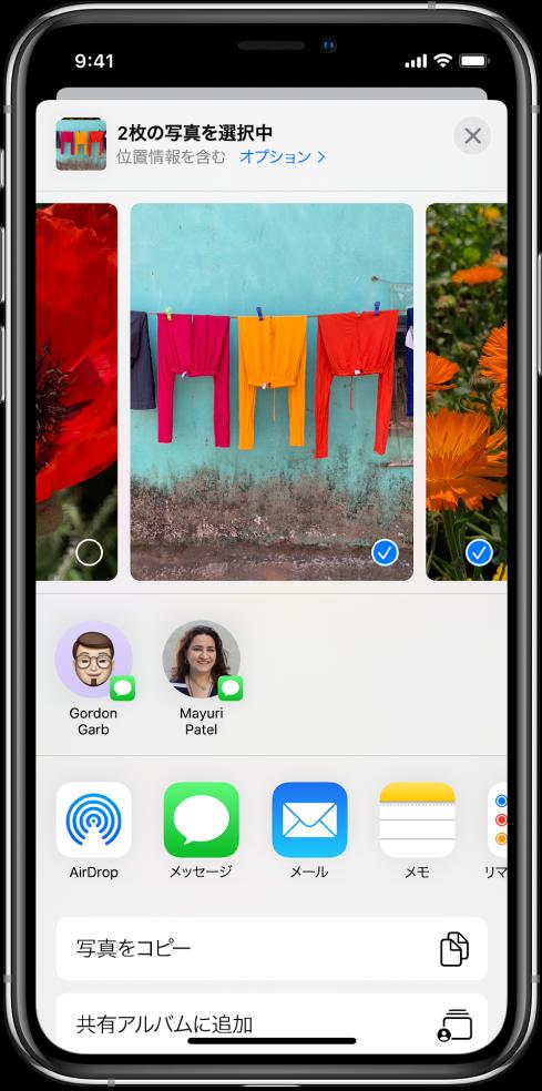 共有画面。上部に写真が並んでいます。選択中の2枚の写真には、白抜きのチェックマークが入った青い円が付いています。写真の下には、AirDropで共有できる友達が表示されています。その下には、左から順に「メッセージ」、「メール」、「共有アルバム」、「メモに追加」などの共有オプションが並んでいます。一番下には、「コピー」、「iCloudリンクをコピー」、「スライドショー」、「AirPlay」、「アルバムに追加」ボタンがあります。
