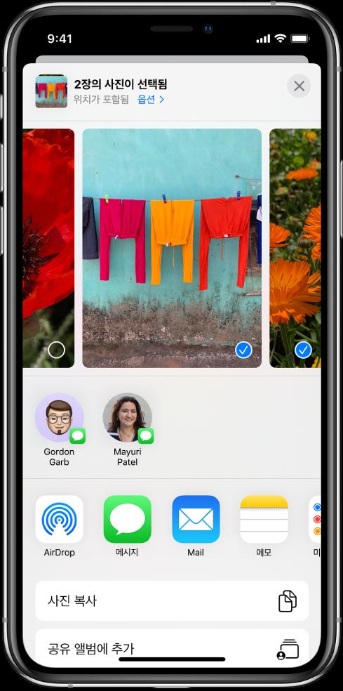 상단에 사진이 있는 공유 화면, 두 개의 사진이 선택되어 있고 파란색 원에 흰색 체크 표시가 되어 있음. 사진 아래의 행에는 AirDrop을 사용하여 사진을 공유할 수 있는 친구가 표시됨. 그 아래에는 왼쪽부터 오른쪽으로 메시지, Mail, 공유 앨범 및 메모에 추가를 포함하는 다른 공유 옵션이 있음. 하단에는 복사하기, iCloud 링크 복사, 슬라이드쇼, AirPlay 및 앨범에 추가 버튼이 있음.