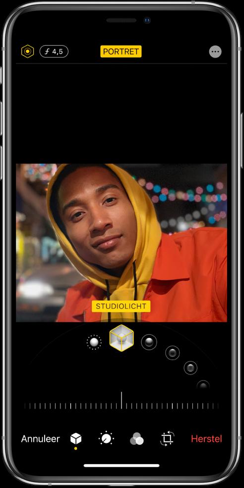 Het scherm 'Wijzig' van een portretfoto. Linksboven in het scherm staan de knoppen waarmee je de intensiteit van de belichting en de scherptediepte aanpast. Middenboven in het scherm is de knop 'Portret' ingeschakeld en rechtsbovenin staat de knop 'Plug-ins'. De foto bevindt zich in het midden van het scherm en onder de foto bevindt zich een schuifknop om het portretbelichtingseffect te kiezen, met daaronder een schuifknop om de waarde aan te passen. Onder in het scherm bevinden zich van links naar rechts de knoppen 'Annuleer', 'Portret', 'Pas aan', 'Filters', 'Snij bij' en 'Herstel'.