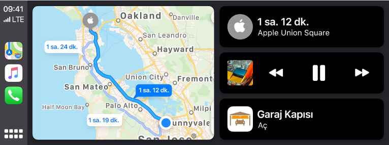Solda Harita, Müzik ve Telefon için simgelerin, ortada araba sürme güzergâhının bir haritasının ve sağda üç öğenin üst üste gösterildiği CarPlay Dashboard. Sağda üstteki öğe Apple Union Square'e tahmini yolculuk süresinin 1 saat 12 dakika olduğunu gösteriyor. Sağdaki orta öüe ortam çalma denetimlerini gösteriyor. Alttaki öğe garaj kapısının açık olduğunu belirtiyor.