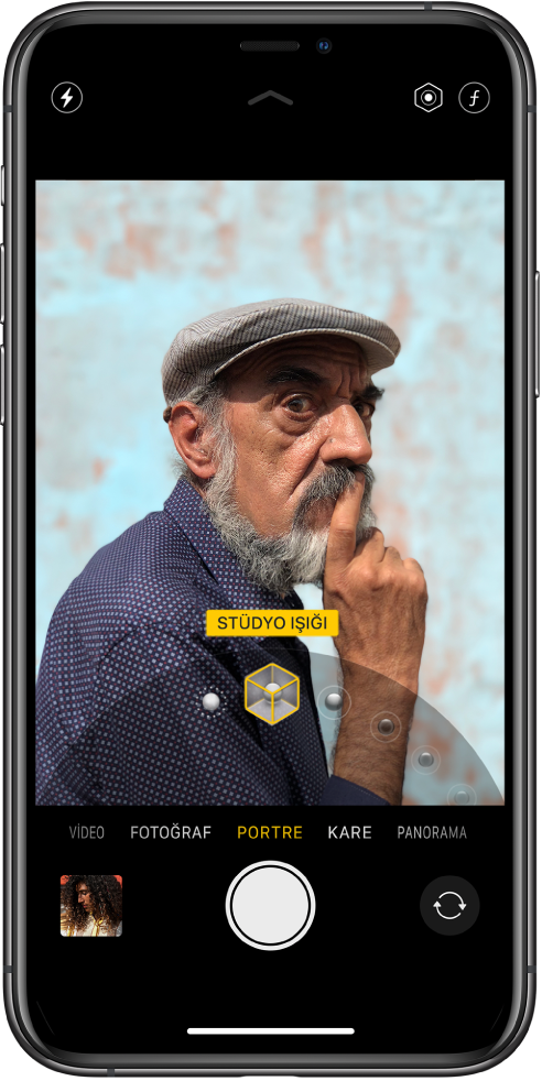 Portre modunun seçili olduğu Kamera ekranı. Görüntüleyicide Portre Işığı seçeneğinin Stüdyo Işığı'na ayarlandığını gösteren bir kutu ve aydınlatma seçeneğini değiştirme sürgüsü var.