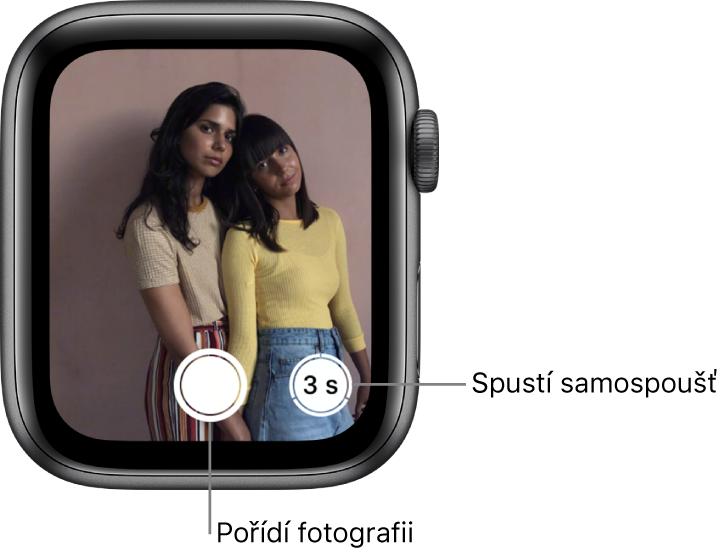 """Když používáte hodinky AppleWatch jako ovladač Fotoaparátu, na jejich obrazovce se zobrazuje to, co je vhledáčku iPhonu. Tlačítko """"Pořídit obrázek"""" se nachází dole uprostřed atlačítko """"Pořídit obrázek po prodlevě"""" vpravo od něj. Po pořízení fotografie vidíte vlevo dole tlačítko Prohlížeč fotografií."""