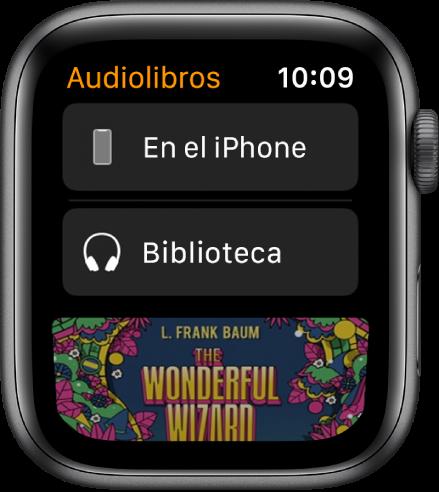 """Apple Watch mostrando la pantalla Audiolibros con el botón """"En el iPhone"""" en la parte superior, el botón Biblioteca debajo y una parte de la portada del audiolibro en la parte inferior."""
