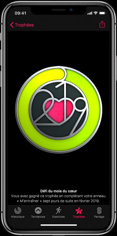 L'onglet Trophées de l'écran de l'app Activité sur l'iPhone, affichant un trophée au centre de l'écran. Vous pouvez faire glisser le trophée pour le faire pivoter. Le bouton Partager se trouve en haut à gauche.