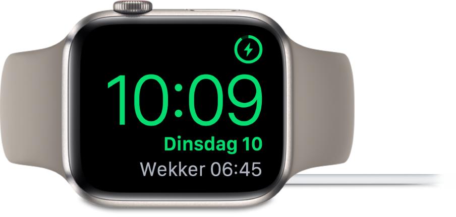 Een AppleWatch die op zijn kant ligt en is aangesloten op de oplader. Rechtsbovenin zie je het oplaadsymbool, en daaronder de actuele tijd en de tijd van de volgende wekker.