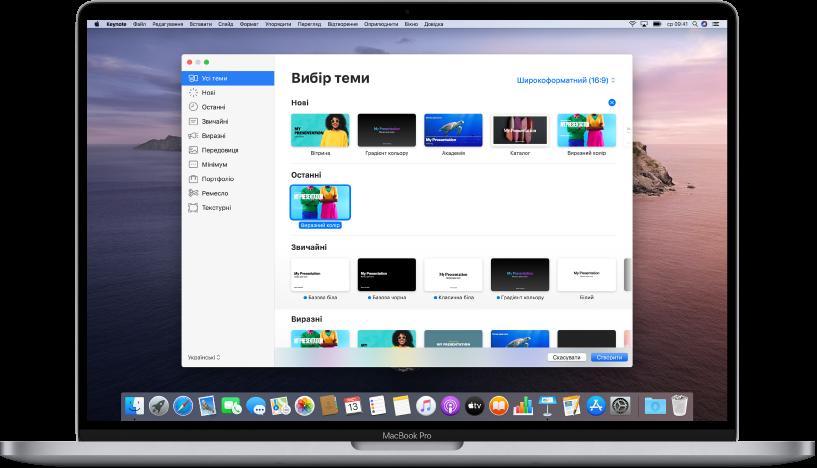 MacBook Pro та відкритий селектор тем Keynote на його екрані. Вибрана ліворуч категорія «Всі теми», а також стандартні теми праворуч, впорядковані в рядки за категоріями. Спливне меню «Мова й регіон» в нижньому лівому кутку і спливн меню «Стандартний» і «Широкий» у правому верхньому кутку.