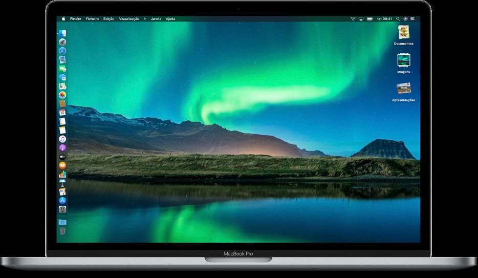 Uma secretária de Mac com o modo escuro, uma imagem de secretária personalizada, a Dock posicionada na extremidade esquerda do ecrã e pilhas na secretária ao longo da extremidade direita do ecrã.