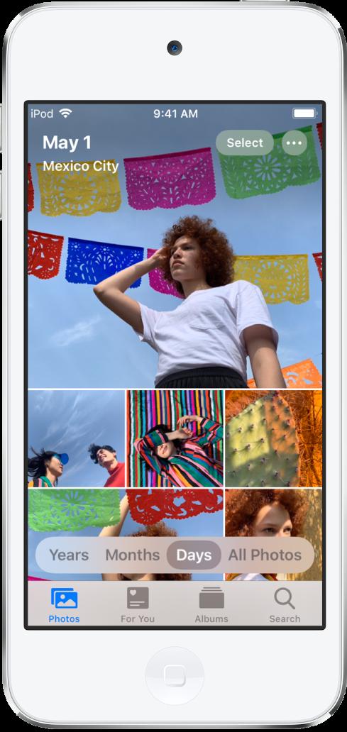 """Die Fotomediathek in der Tagesansicht. Eine Auswahl mit Fotominiaturen füllt den Bildschirm. Oben links wird angezeigt, wann und wo die Fotos aufgenommen wurden. Oben rechts befinden sich die Tasten """"Auswählen"""" und """"Weitere Optionen"""". Unter den Miniaturen befinden Optionen zum Anzeigen aller Fotos in der Fotomediathek oder unterteilt nach Jahren, Monaten oder Tagen. Ganz unten befinden sich die Tabs """"Fotos"""", """"Für dich"""", """"Alben"""" und """"Suchen""""."""