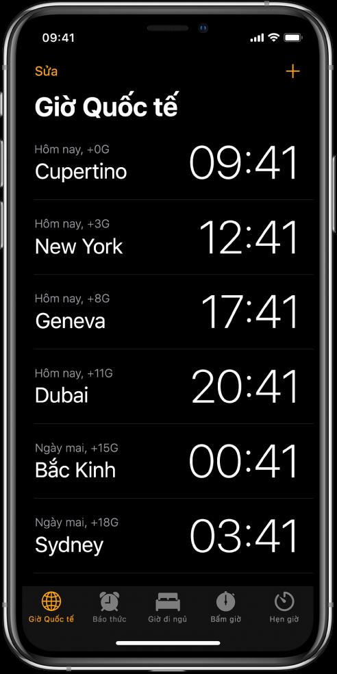 Tab Giờ quốc tế, đang hiển thị thời gian tại nhiều thành phố. Chạm vào Sửa ở phía trên bên trái để sắp xếp các đồng hồ. Chạm vào nút Thêm ở phía trên bên phải để thêm đồng hồ khác. Các nút Báo thức, Giờ đi ngủ, Bấm giờ và Hẹn giờ nằm ở dưới cùng.