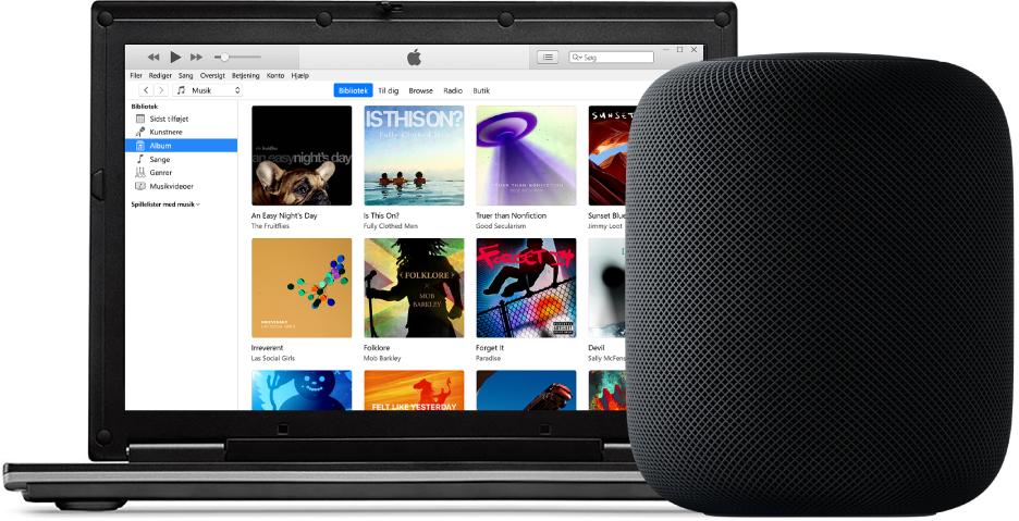 En pc med iTunes på skærmen og en HomePod ved siden af.
