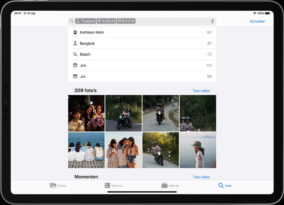 Foto's is geopend in de liggende weergave. Onder in het scherm bevinden zich van links naar rechts de knoppen 'Foto's', 'Voor jou', 'Albums' en 'Zoek'. 'Zoek' is geselecteerd. Boven in het scherm bevindt zich een zoekveld. In het zoekveld worden een locatie en data ingevuld. Onder het zoekveld worden zoekresultaten weergegeven. In het midden van het scherm bevindt zich een raster met foto's die zijn gebaseerd op de zoektermen. Links boven het fotoraster staat het totaal aantal foto's in het zoekresultaat. Rechts boven het fotoraster staat een knop 'Toon alles'.