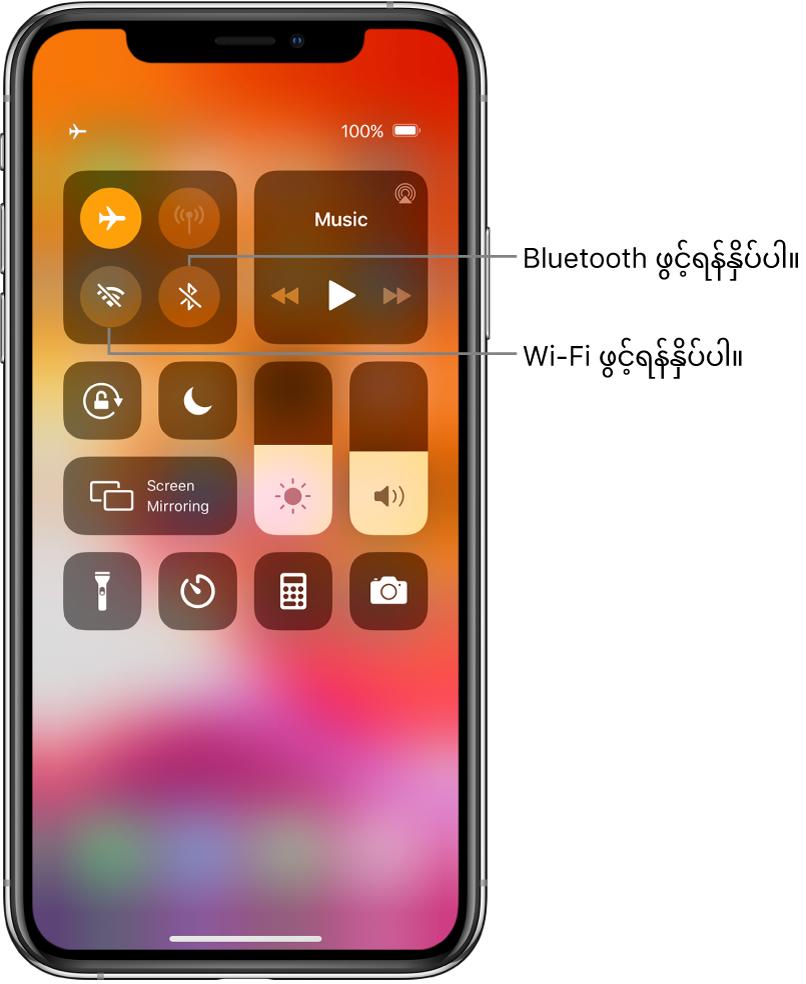 လေယာဉ်စီးသည့်စနစ်ဖွင့်ထားသည့် Control Center ပုံ၊ ၎င်းတွင် Wi-Fi ဖွင့်လိုလျှင် ဘယ်ဘက်ထိပ်ရှိ ထိန်းချုပ်မှုအုပ်စုတွင်းက ဘယ်ဘက်အောက်ခြေခလုတ်ကို နှိပ်ရန်၊ Bluetooth ကို ဖွင့်လိုလျှင် အဆိုပါအုပ်စုတွင်းရှိ ညာဘက်အောက်ခြေခလုတ်ကို နှိပ်ရန် ရှင်းပြထားသည့် စကားပြောပုံစံတစ်ခုပါသည်။