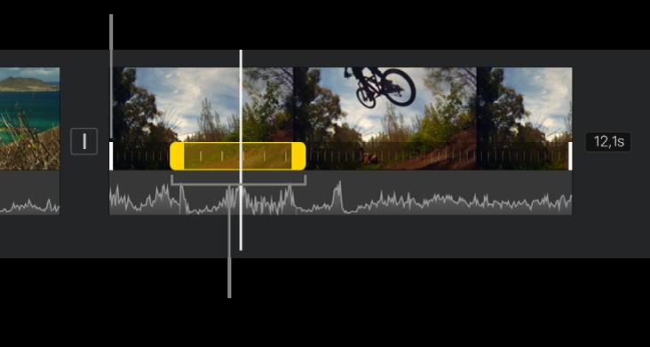 Un interval de velocitat amb tiradors d'interval grocs en un clip de vídeo a la línia de temps, amb línies blanques al clip que indiquen les vores de l'interval.