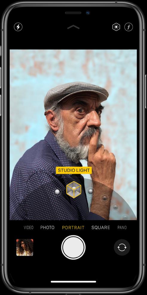 Екран на Camera (Камера) в режим Portrait (Портрет), обектът е на ясен фокус, а фонът е замъглен. Колелото за избор на ефектите за портретно осветление е отворено в долния край на рамката и е избран ефект Studio Light (Студийно осветление). Горе вляво на екрана е бутонът Flash (Светкавица), а горе вдясно са бутоните за настройване на интензитета на портретното осветление и на дълбочината на рязкост. Близо до долния край на екрана са, от ляво надясно, иконка на умалено изображение за достъп до снимки и видео, бутонът Shutter (Снимане) и бутонът Switch Camera (Превключване на камерата).
