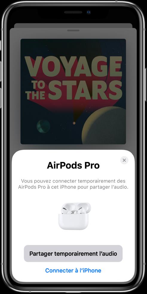 Un écran d'iPhone avec une image d'AirPods dans un boîtier de charge ouvert. vers le bas de l'écran se trouve un bouton permettant de partager temporairement du contenu audio.