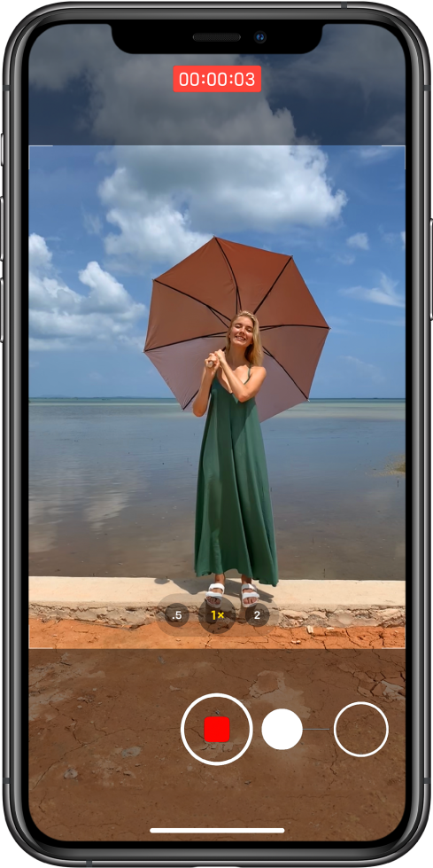 """Kameros ekranas """"Photo"""" režimu. Objektas yra ekrano centre, viduje kameros rėmų. Ekrano apačioje """"Shutter"""" mygtukas juda į dešinę, parodydamas """"QuickTake"""" vaizdo įrašo pradėjimą. Įrašymo laikmatis yra ekrano viršuje."""