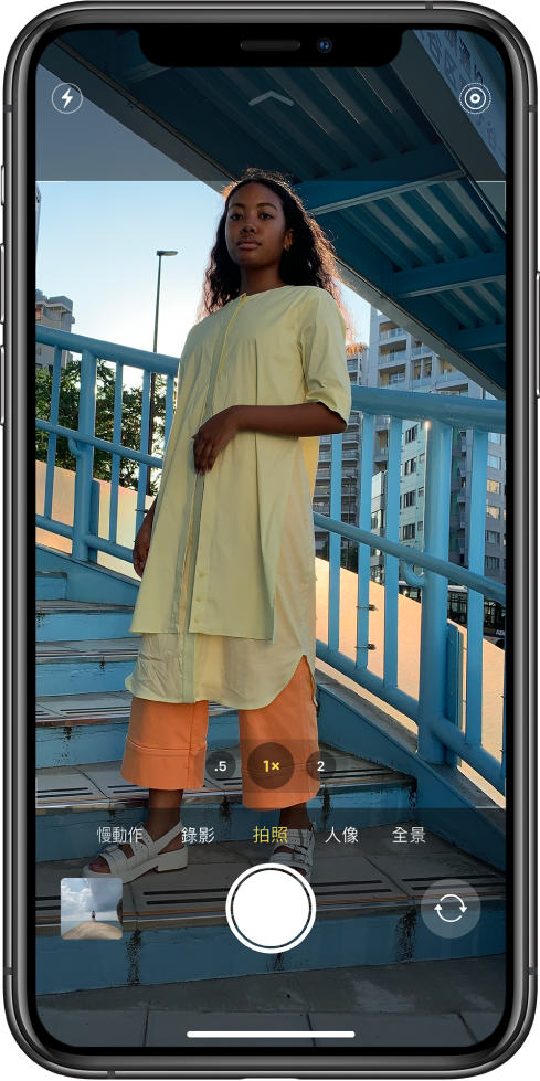 「相機」處於「拍照」模式,其他模式位於取景窗下方左右兩側。「閃光燈」、「夜間」模式和「原況照片」的按鈕顯示於螢幕最上方。照片和影片檢視器位於左下角。「快門」按鈕位於底部中央,而相機選擇器按鈕位於右下方。