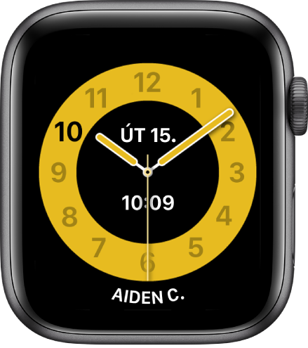 Ciferník Čas ve škole se zobrazeným ručičkovým číselníkem asdatem adigitálním časovým údajem poblíž středu. Úplně dole je jméno uživatele hodinek