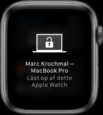 """Skærm på Apple Watch, der viser beskeden """"Marc Krochmals MacBook Pro er låst op af dette Apple Watch""""."""