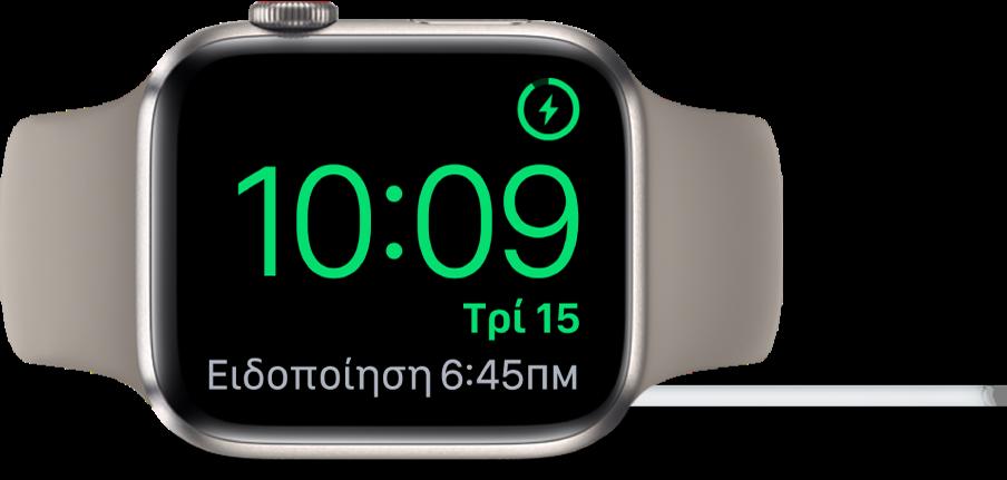 Ένα AppleWatch τοποθετημένο στο πλάι του και συνδεδεμένο στον φορτιστή του. Στην οθόνη εμφανίζεται το σύμβολο φόρτισης στην πάνω δεξιά γωνία, η τρέχουσα ώρα από κάτω η ώρα του επόμενου ξυπνητηριού.
