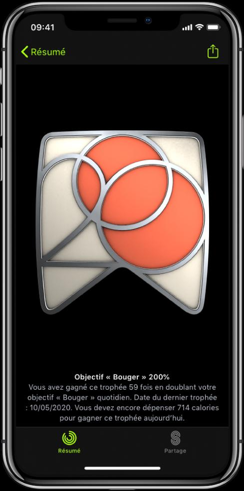 L'onglet Trophées de l'écran de l'app Forme sur l'iPhone, affichant un trophée au centre de l'écran. Vous pouvez faire glisser le trophée pour le faire pivoter. Le bouton Partager se trouve en haut à gauche.