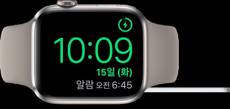 AppleWatch가 옆으로 누워있고 충전기에 연결되어 있음. 화면의 오른쪽 상단 모서리에는 충전 기호가 있고 그 아래에는 현재 시간과 다음 알람 시간이 있음.