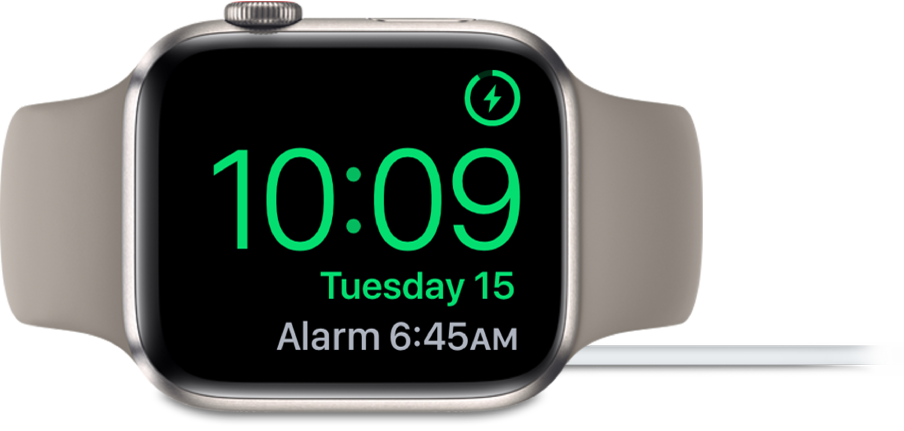 Apple Watch pulkstenis ir novietots uz sāniem un pievienots lādētājam. Tā ekrāna augšējā labajā stūrī ir redzams uzlādes simbols, zem tā ir parādīts pašreizējais laiks, kā arī nākamā modinātāja laiks.
