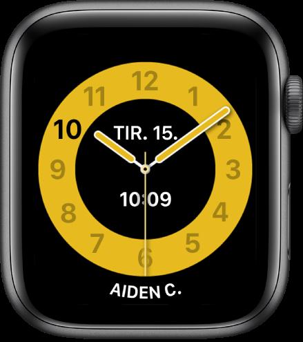 Skoletid-urskiven som viser en analog klokke med dato og digitalt klokkeslett ved midten. Nederst er navnet på personen som bruker klokken.