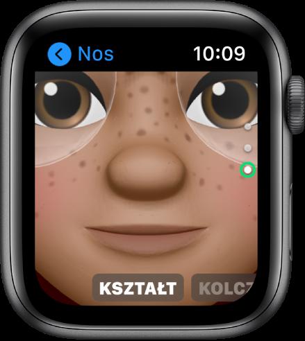 Aplikacja Memoji na AppleWatch, wyświetlająca ekran edycji nosa. Widoczne jest zbliżenie na twarz, koncentrujące się na nosie. Na dole znajduje się etykieta Kształt.