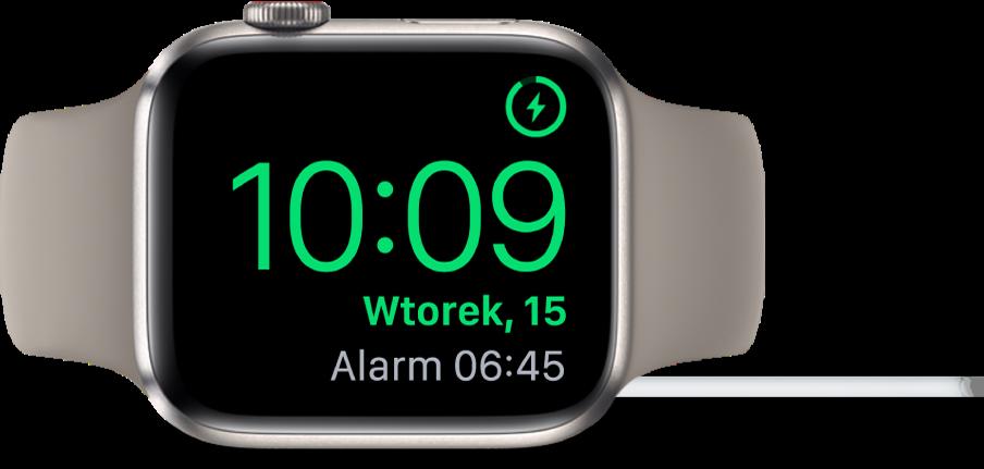 AppleWatch ustawiony na boku ipodłączony do ładowarki. Wprawym górnym rogu ekranu widoczny jest symbol ładowania, niżej wyświetlana jest bieżąca godzina, adalej znajduje się czas najbliższego alarmu.
