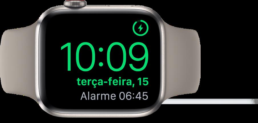 Um AppleWatch colocado de lado e ligado ao carregador, com o ecrã a mostrar o símbolo de carregamento no canto superior direito e, por baixo, a hora atual e a hora do próximo alarme.