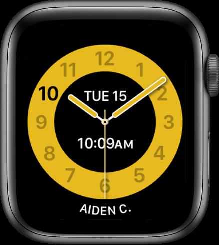 Številčnica Schooltime (Čas za šolo) prikazuje analogno uro z datumom blizu vrha in časom pod njim. Na dnu je prikazano ime osebe, ki uporablja uro.