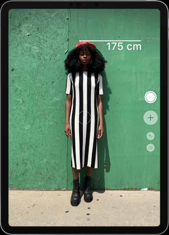 """Die Größe einer Person wird gemessen, die gemessene Größe wird oben über dem Kopf der Person angezeigt. Die Taste """"Bild aufnehmen"""" an der rechten Kante ist aktiv und kann zum Aufnehmen eines Bilds von der Messung verwendet werden. Das grüne Symbol """"Kamera wird verwendet"""" wird oben rechts angezeigt."""