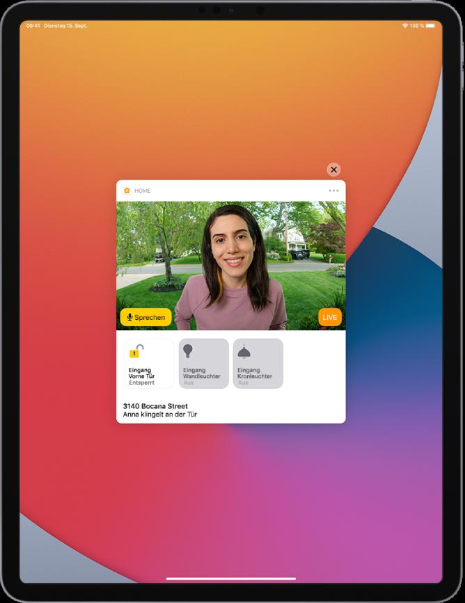 """Auf dem Bildschirm des iPad wird eine Mitteilung der App """"Home"""" angezeigt. Sie zeigt das Bild einer Person, die vor der Tür steht. Links befindet sich eine Sprechtaste. Darunter sind Tasten für die Haustür und die Beleuchtung des Eingangsbereichs. Die Adresse befindet sich unten und es wird der Text """"Anna klingelt an der Tür"""" angezeigt. Oben rechts neben der Mitteilung befindet sich die Taste """"Schließen""""."""