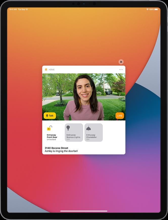 """iPadi ekraanil kuvatakse rakenduse Home märguannet. Sellel on välisukse taga oleva inimese pilt koos nupuga Talk vasakul. All on lisaseadmete nupud välisukse ja esikutulede jaoks. Allservas on kodu aadress koos sõnadega """"Ashley is ringing the doorbell."""" Märguande ülemises paremas servas on nupp Close."""