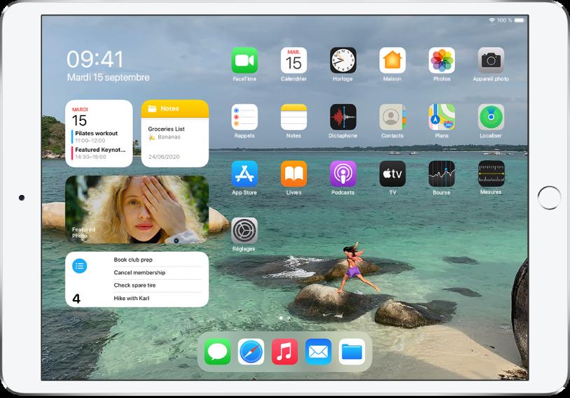 L'écran d'accueil de l'iPad. Sur le côté gauche de l'écran se trouve l'affichage du jour, montrant les widgets Calendrier, Notes, Photos et Rappels.