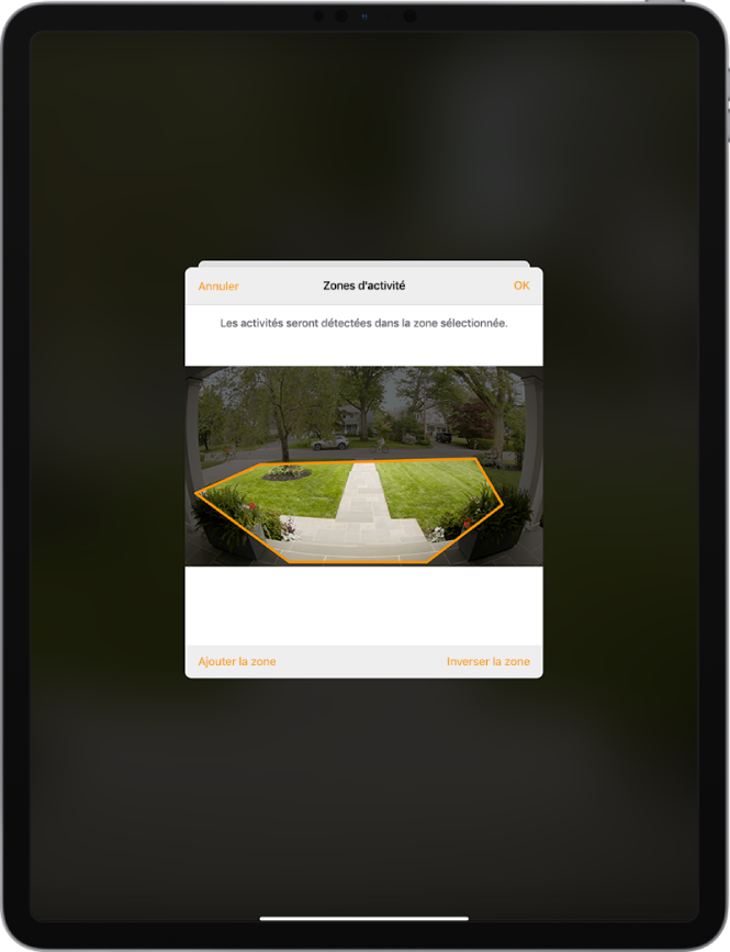 Écran d'iPad montrant une zone d'activité dans une image prise par une caméra de porte. La zone d'activité inclut un perron et une allée, mais exclut la rue et la voie d'accès. Les boutons Annuler et OK se trouvent au-dessus de l'image. Les boutons «Ajouter la zone» et «Inverser la zone» se trouvent en dessous.