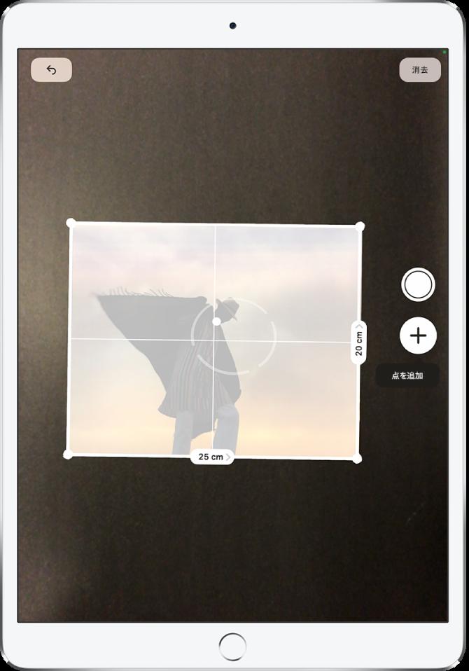 計測している写真。右端と下端に寸法が表示されています。右端の中ほどには写真撮影ボタンがあります。緑色のカメラ使用中インジケータが右上に表示されています。