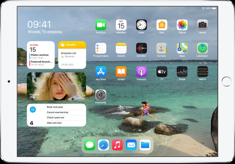 Ekran początkowy iPada. Po lewej stronie ekranu znajduje się widok Dzisiaj, zawierający widżety: Kalendarz, Notatki, Zdjęcia oraz Przypomnienia. Po prawej stronie ekranu widoczne są aplikacje.