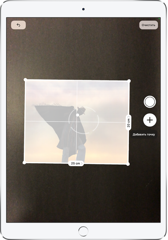 Измерение формата напечатанной фотографии. Вдоль ее правого инижнего краев показаны размеры. Кнопка «Снять фото» расположена посередине у правого края экрана. В правом верхнем углу отображается зеленый индикатор «Камера используется».