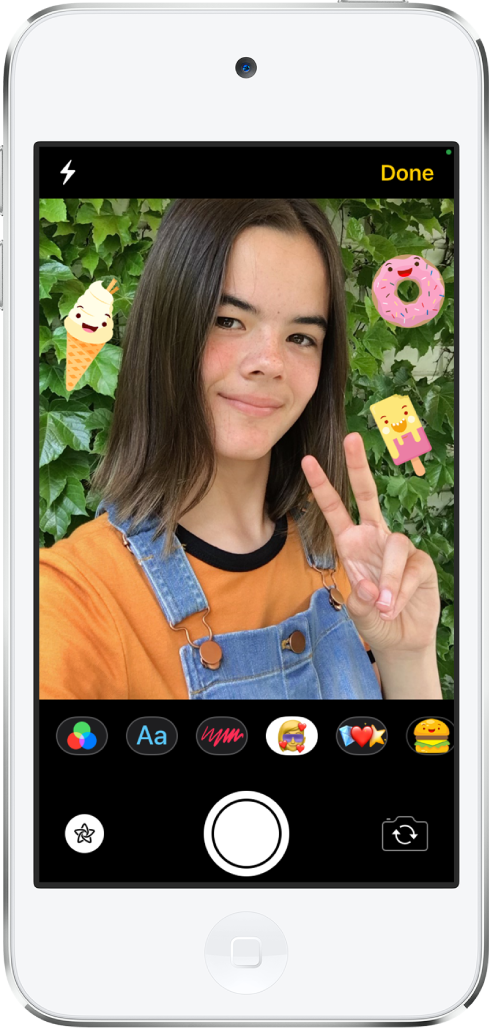 หน้าจอเอฟเฟ็กต์ข้อความ ด้านบนสุดของหน้าจอแสดงกรอบของกล้องด้านหน้า มีสติ๊กเกอร์ iMessage อยู่รอบๆ สิ่งที่อยู่ในกรอบ ด้านล่างกรอบ เรียงจากซ้ายไปขวา คือ ปุ่มฟิลเตอร์ ปุ่มข้อความ ปุ่มรูปร่าง ปุ่ม Memoji ปุ่มอิโมจิ และปุ่มแอพ iMessage ที่ด้านล่างสุดของหน้าจอ เรียงจากซ้ายไปขวา คือ ปุ่มเอฟเฟ็กต์ ปุ่มชัตเตอร์ และปุ่มตัวเลือกกล้องด้านหลัง