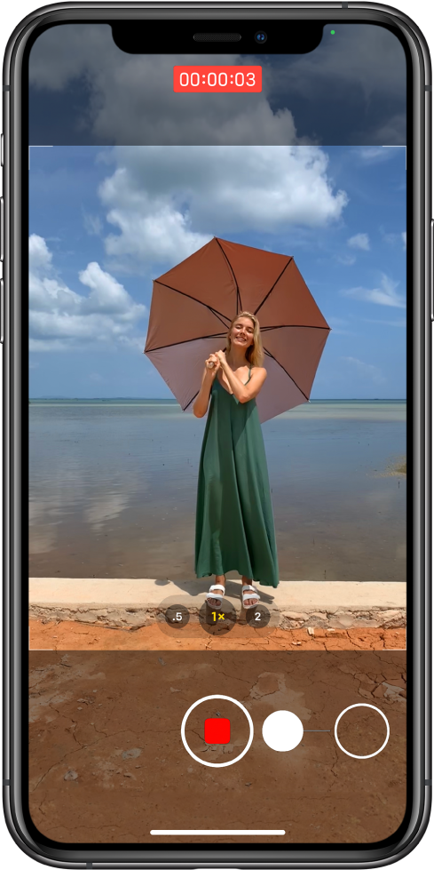 شاشة الكاميرا تعرض حركة بدء تسجيل فيديو QuickTake. بالقرب من الجزء السفلي للشاشة، يتحرك زر الغالق يسارًا ناحية زر القفل، للإشارة إلى إيماءة بدء فيديو QuickTake في نمط صورة. مؤقت التسجيل في أعلى الشاشة.