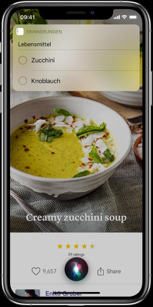 """Als Antwort auf die Anfrage """"Füge Zucchini und Knoblauch zu meiner Einkaufsliste hinzu"""" zeigt Siri eine Erinnerungsliste mit dem Titel """"Lebensmittel"""" an. Die Liste wird über einem Rezept für eine Zucchinicremesuppe angezeigt."""