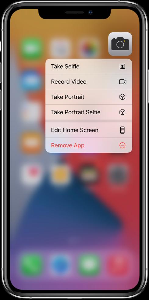 Aizmiglots sākuma ekrāns, kurā zem lietotnes Camera ikonas ir redzama kameras ātro darbību izvēlne.