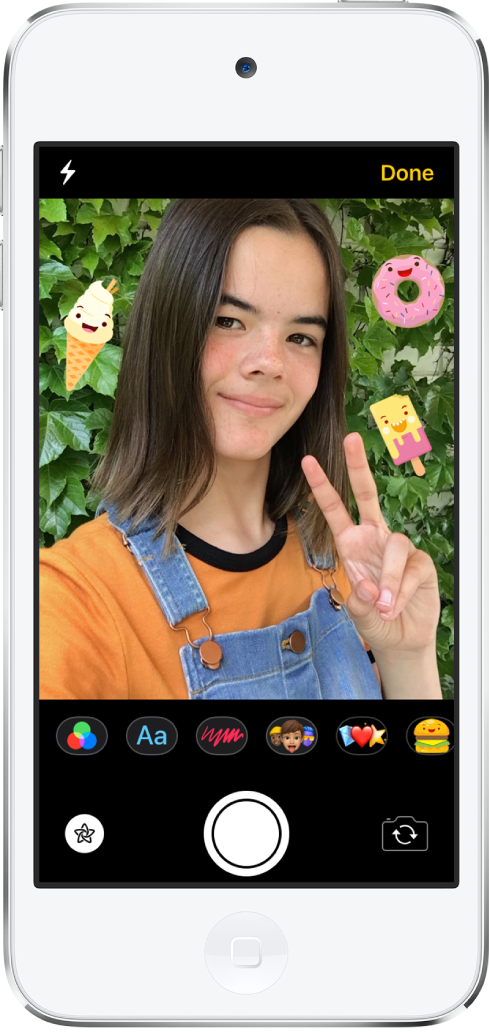 The Messages effects screen. The top of the screen shows the front camera frame. iMessage stickers are around the subject in the frame. Below the frame, from left to right, are the filters, text, shapes, Memoji, Animoji, and iMessage app buttons. At the bottom of the screen, from left to right, are the Effects, Shutter, and Camera Chooser buttons.