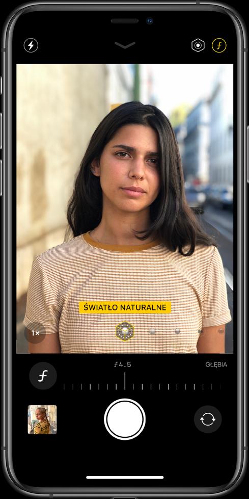 Ekran aplikacji Aparat wtrybie portretowym. Przycisk korekcji efektu głębi jest wybrany wprawym górnym rogu ekranu. Pole wwizjerze aparatu wskazuje, że opcja oświetlenia portretowego jest ustawiona na światło naturalne. Wyświetlany suwak pozwala zmienić opcję oświetlenia. Pod wizjerem znajduje się suwak pozwalający zmienić siłę efektu głębi.
